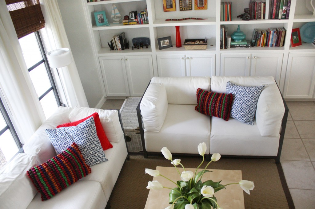 white bookshelves built ins and white leather contemporary couches