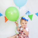 first birthday portrait with balloons and banner