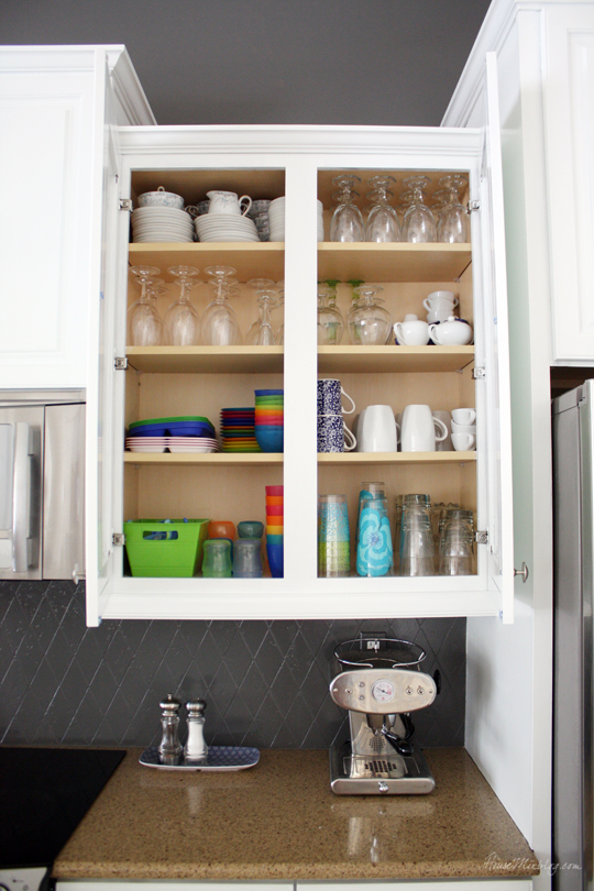 Organized kitchen cabinet with kid dishes and glasses