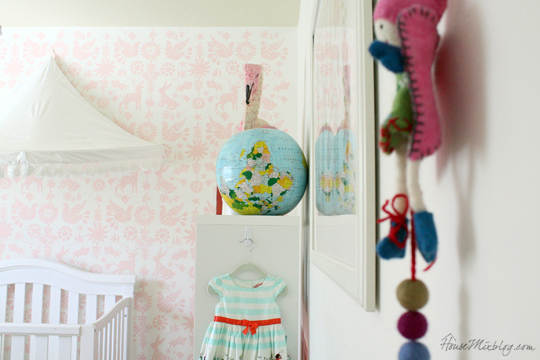 Colorful girls nursery with stenciled wall and pom pom canopy