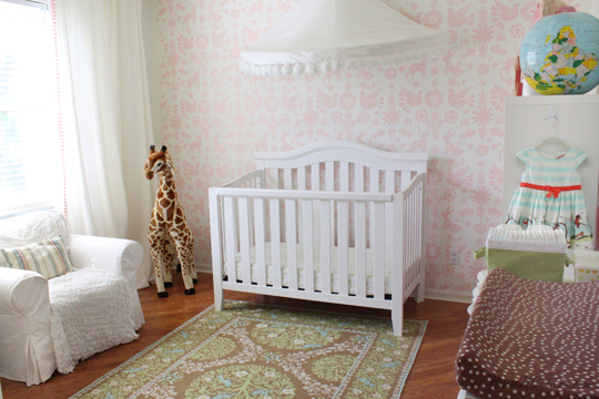 Girls nursery with pink Mexican otomi pattern and white pom pom curtain