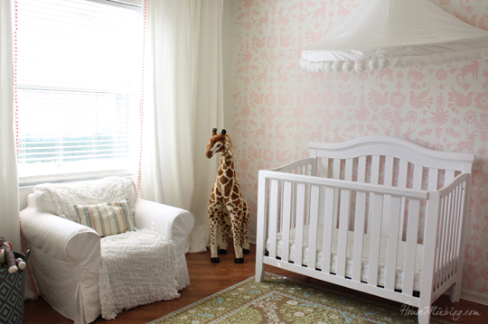 Nursery with pink Mexican otomi pattern and white pom pom canopy
