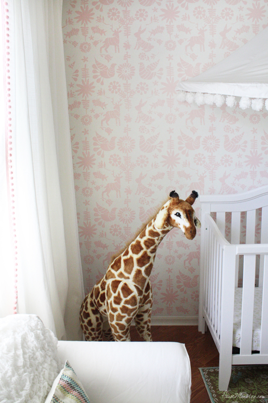 Pink and white nursery with canopy and giraffe