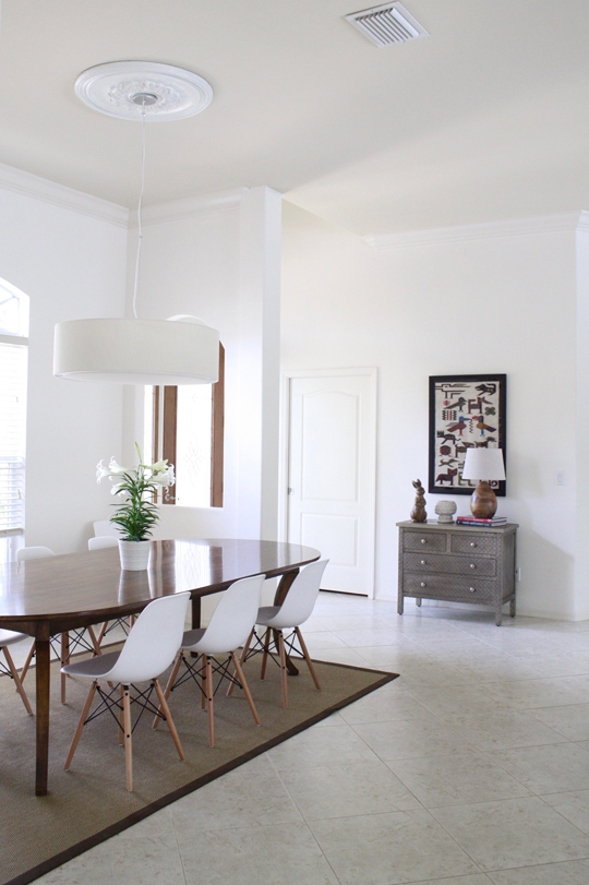 White dining room with wood table and Eames chairs