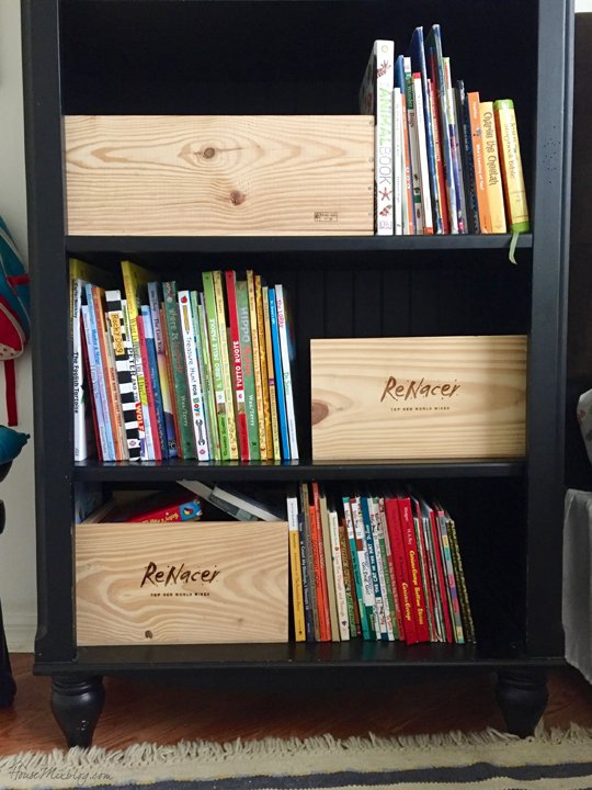 Black bookshelf in boys room with boxes to help keep books neat