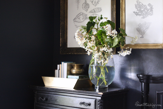 Black dresser with gold tray and gold frames on navy wall