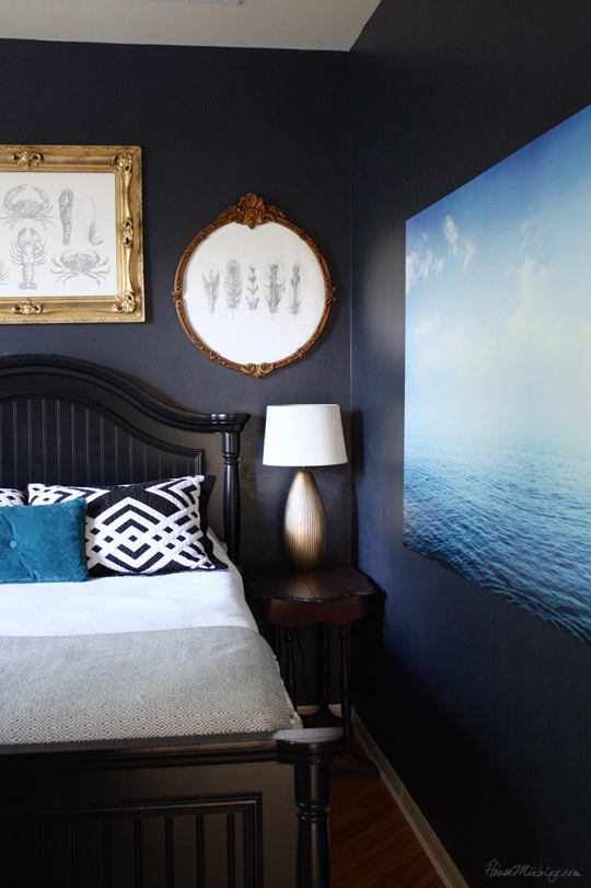 Navy blue bedroom with painted gold frames and diy art