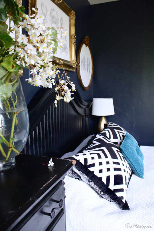 Navy blue, black and gold bedroom with gold frames and understated nautical theme
