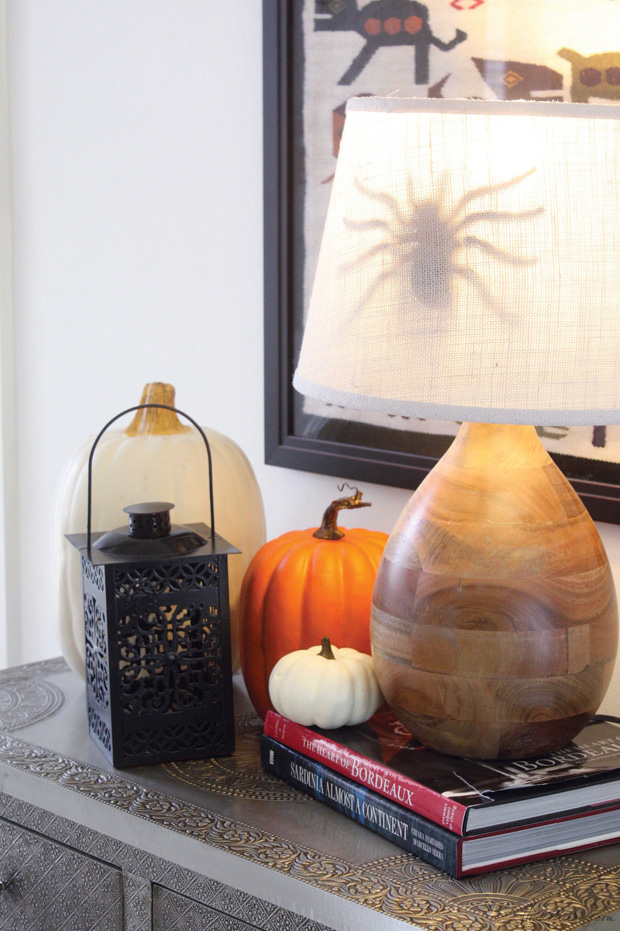 A large dollar store spider behind a lampshade makes a spooky Halloween surprise