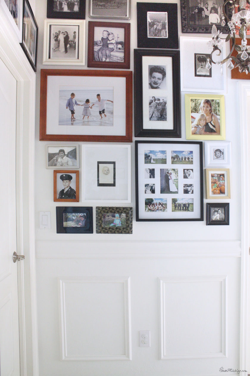 Photo gallery collage covers entire hallway with family photos of new and old. Chair rail and premade moulding frames offer a boundary.