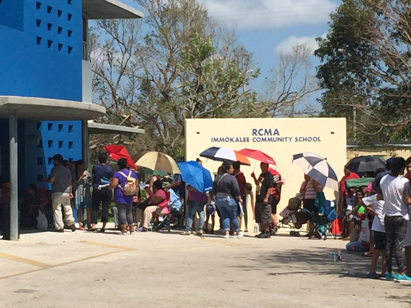 Line of people that goes around the corner, waiting for food and water after hurricane irma.