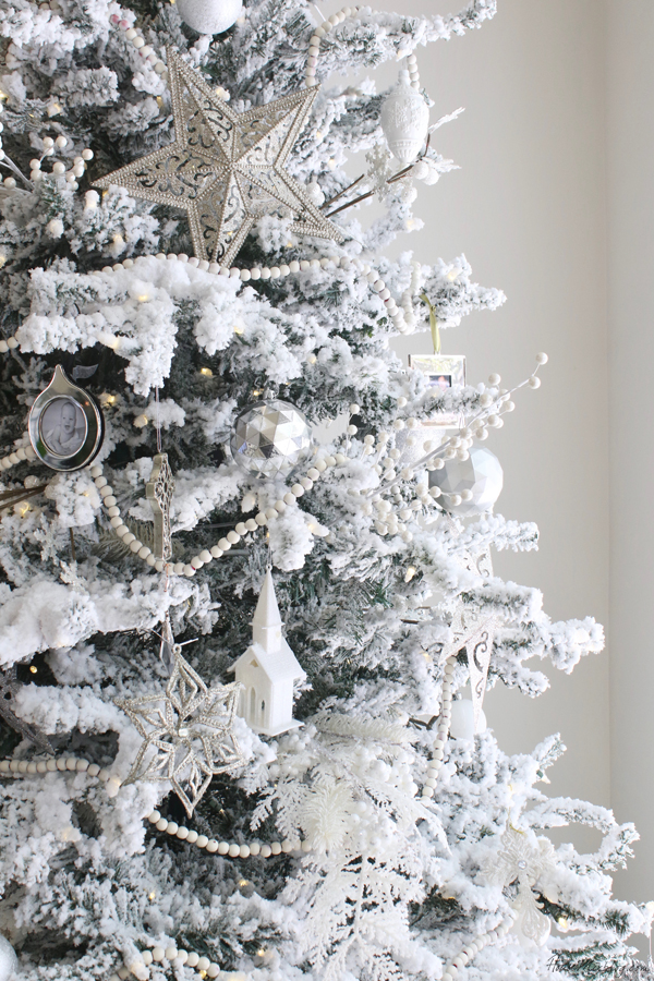 Flocked white Christmas tree with all white and silver decorations and white beads