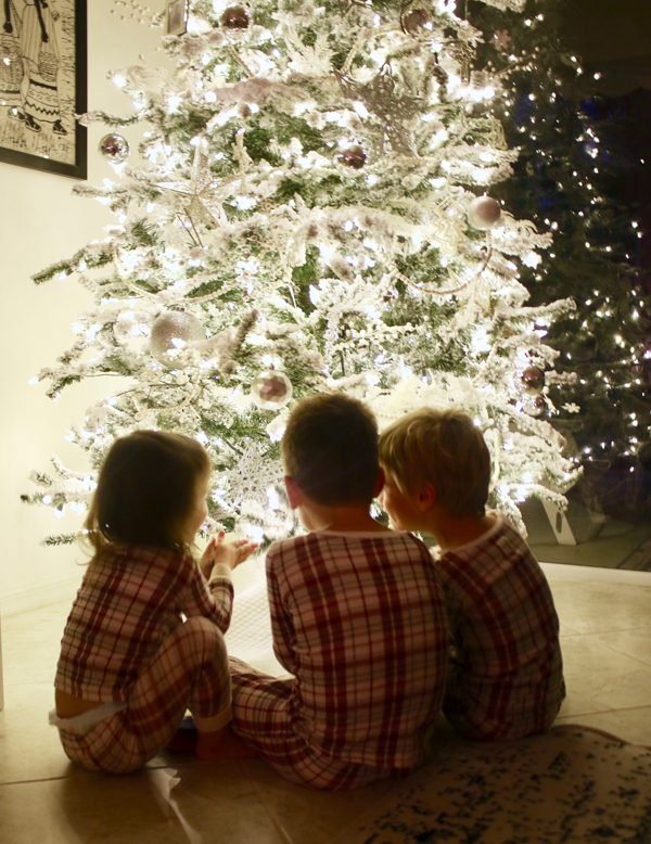 kids around lit Christmas tree