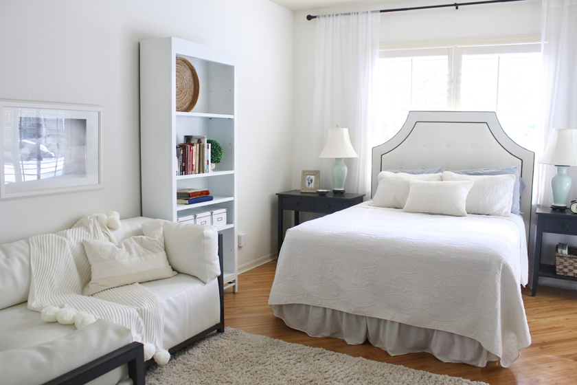 All white bedroom with sofa and gray nightstands