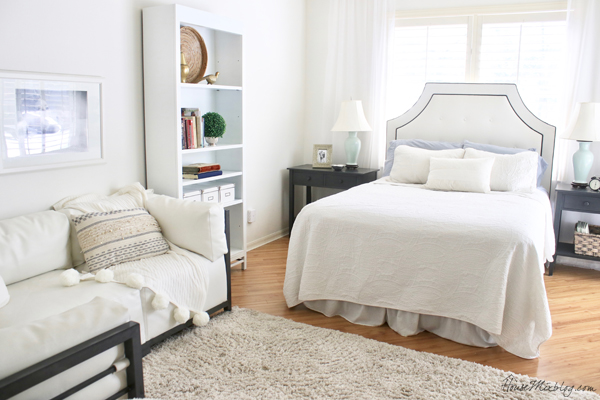 All white bedroom with couch and bookshelf