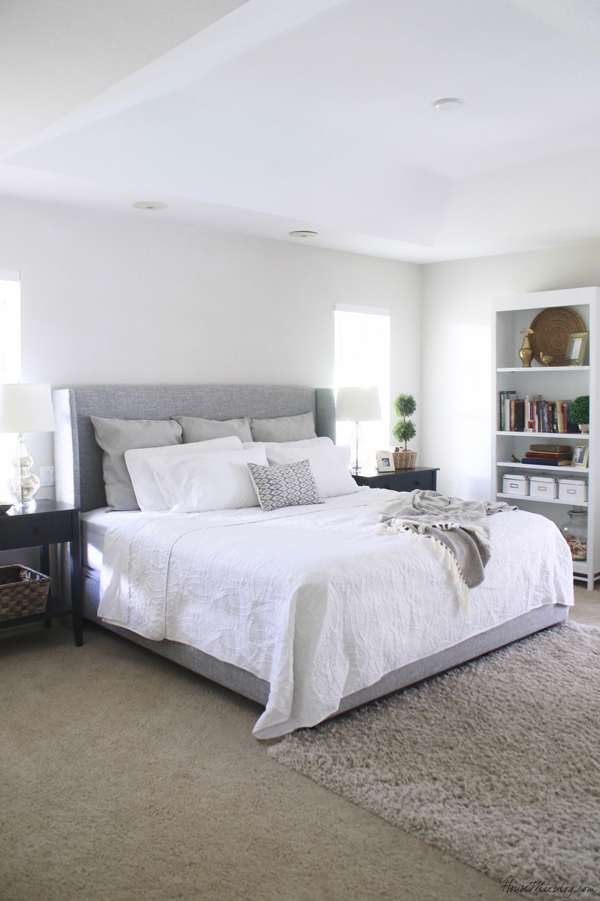 White bedroom with gray upholstered bed and large black nightstands