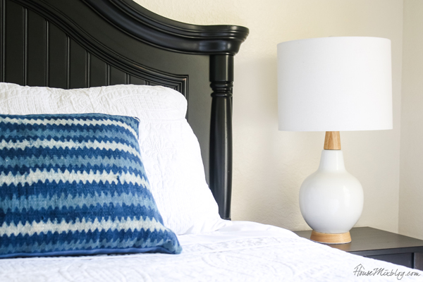 Blue lumbar pillow and white lamp with wood detail