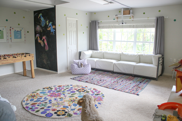 Large playroom layout with chalkboard wall and foosball table and movie projector