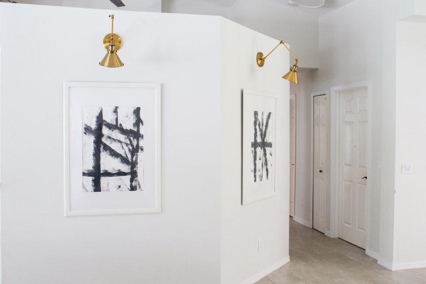 modern black and white DIY art with bronze sconces