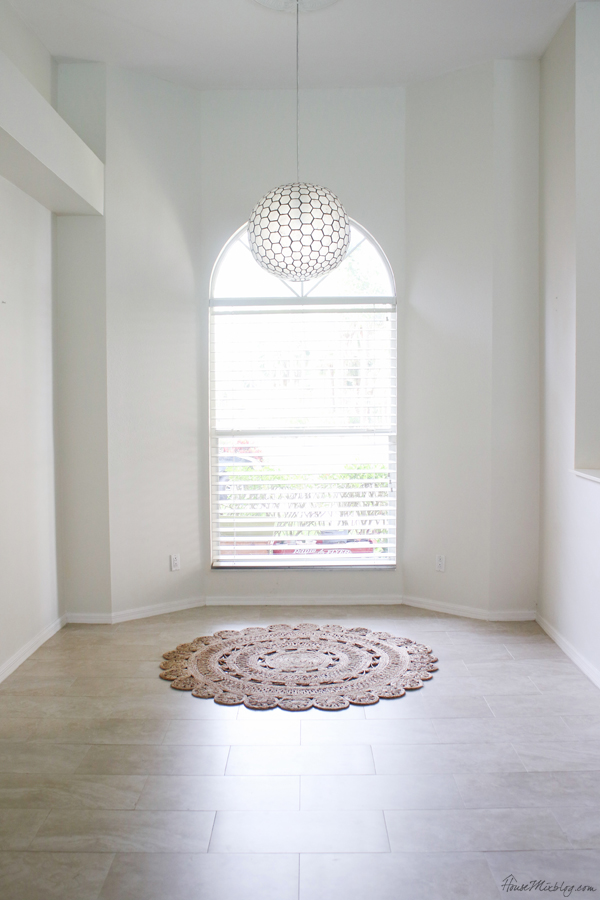 white blank picture window with round jute rug and capiz globe light fixture