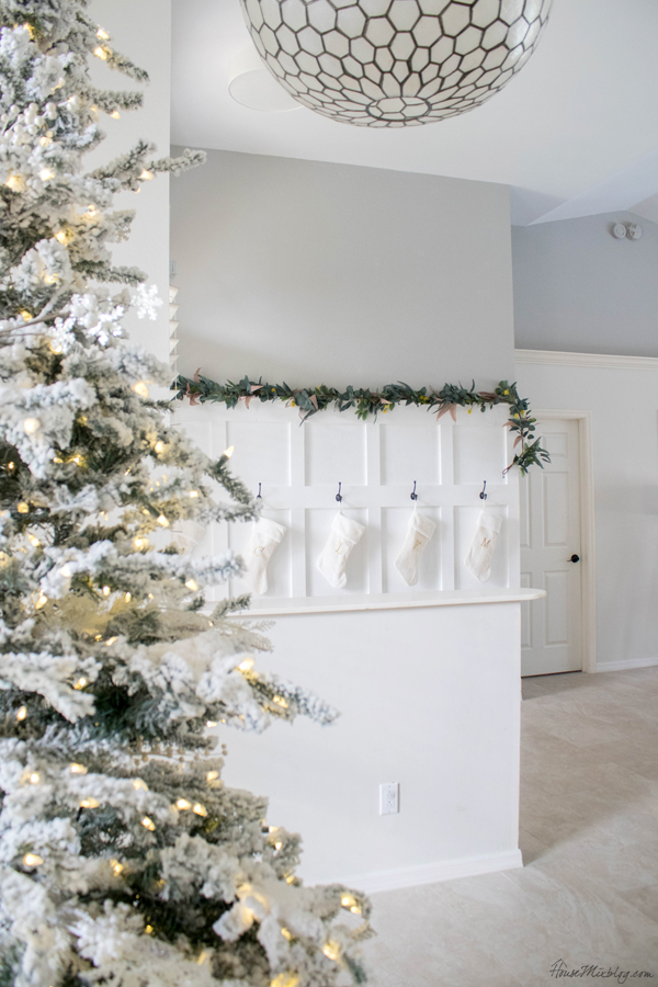 flocked prelit christmas tree without ornaments - white stockings hanging in entryway