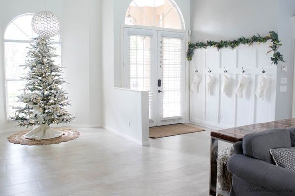 neutral christmas decor - bare Christmas tree, eucalyptus garland, white stockings on board and batten wall with black hooks