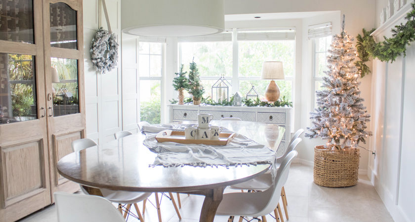 neutral christmas decor - dining room with christmas tree, wreaths, lights, garland, little white houses