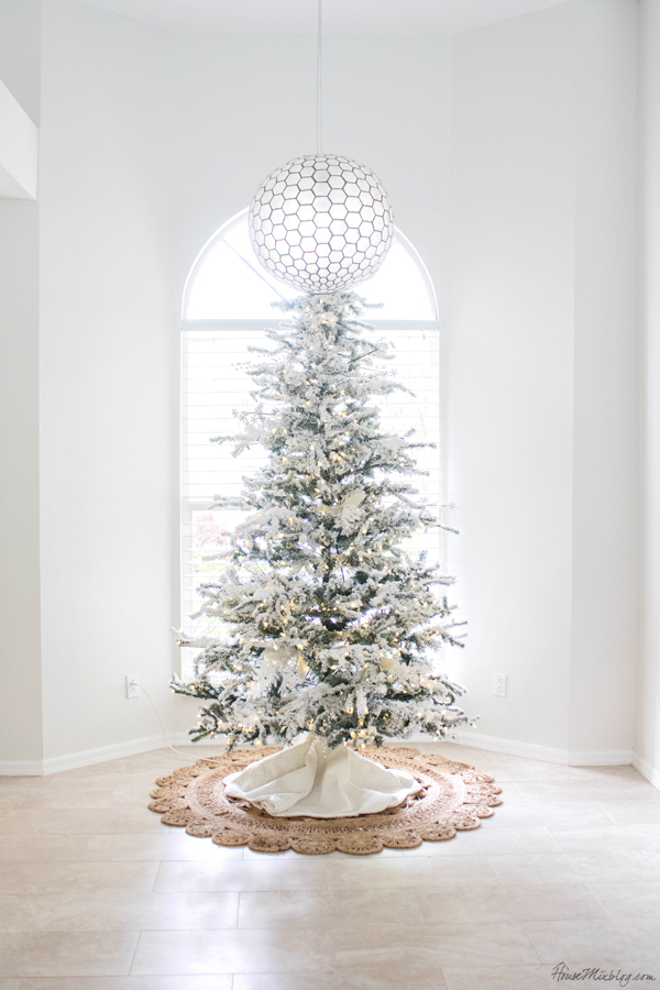 white and bright Christmas decorations - flocked tree in front of window
