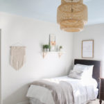Neutral guest room with twin beds, blue ceiling