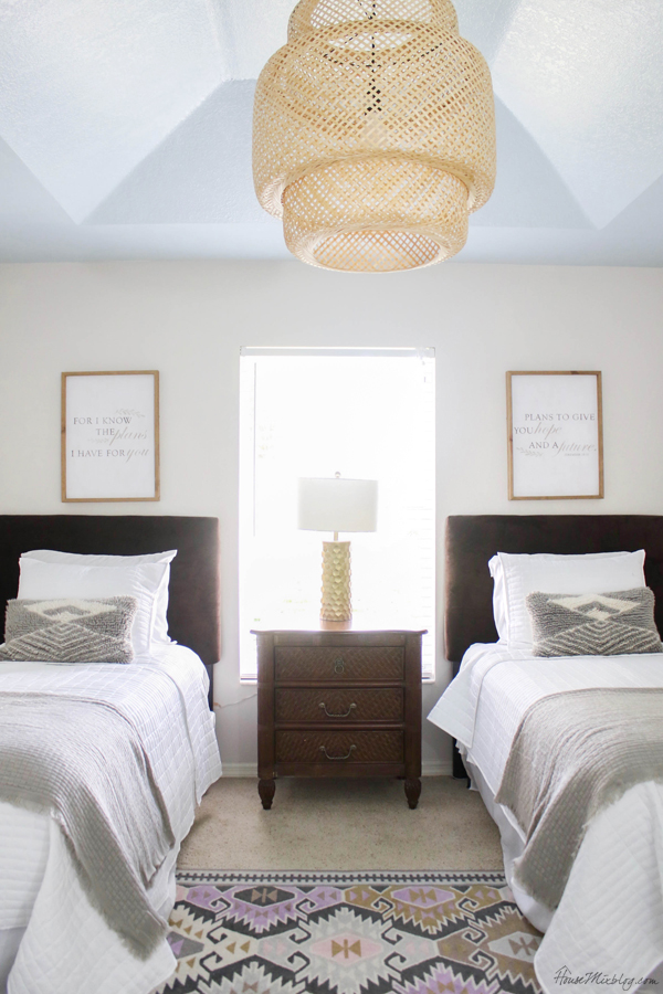 Neutral guest room with two twin beds, bamboo pendant and blue ceiling