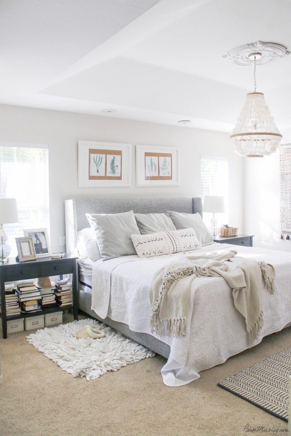 White bedroom with black nightstands and capiz pendant light