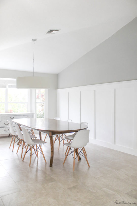 White dining room with large table and board and batten wall