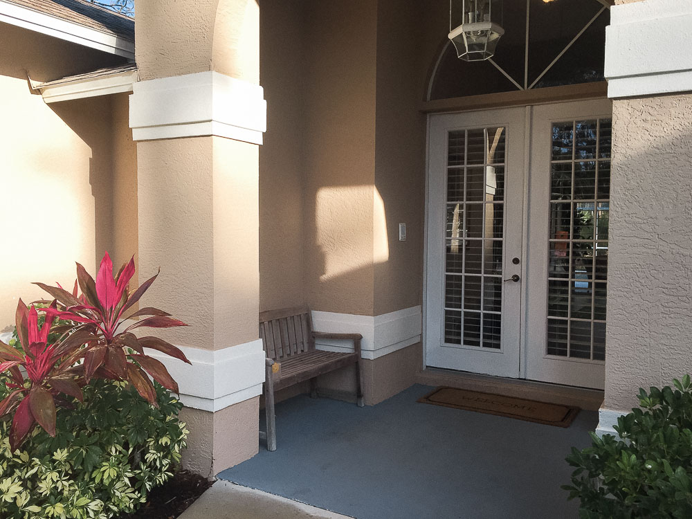 Front porch makeover with paint - -before - beige brown paint and white french doors