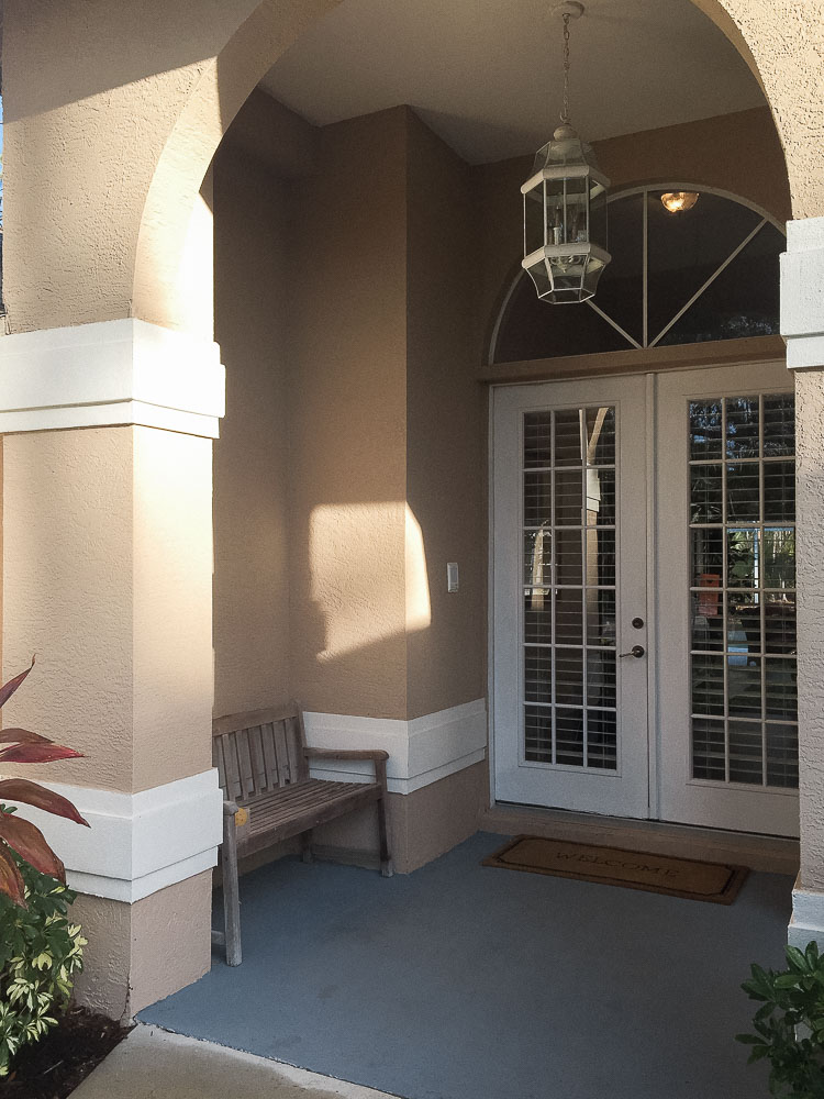 Front porch makeover with paint - before with brown paint and white french doors