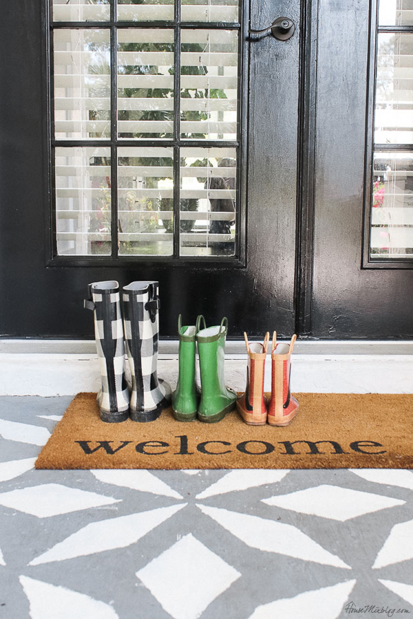 Front porch makeover with paint - welcome mat with rain boots and black door and stenciled floor