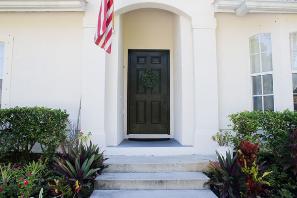 Painted black front door with white house