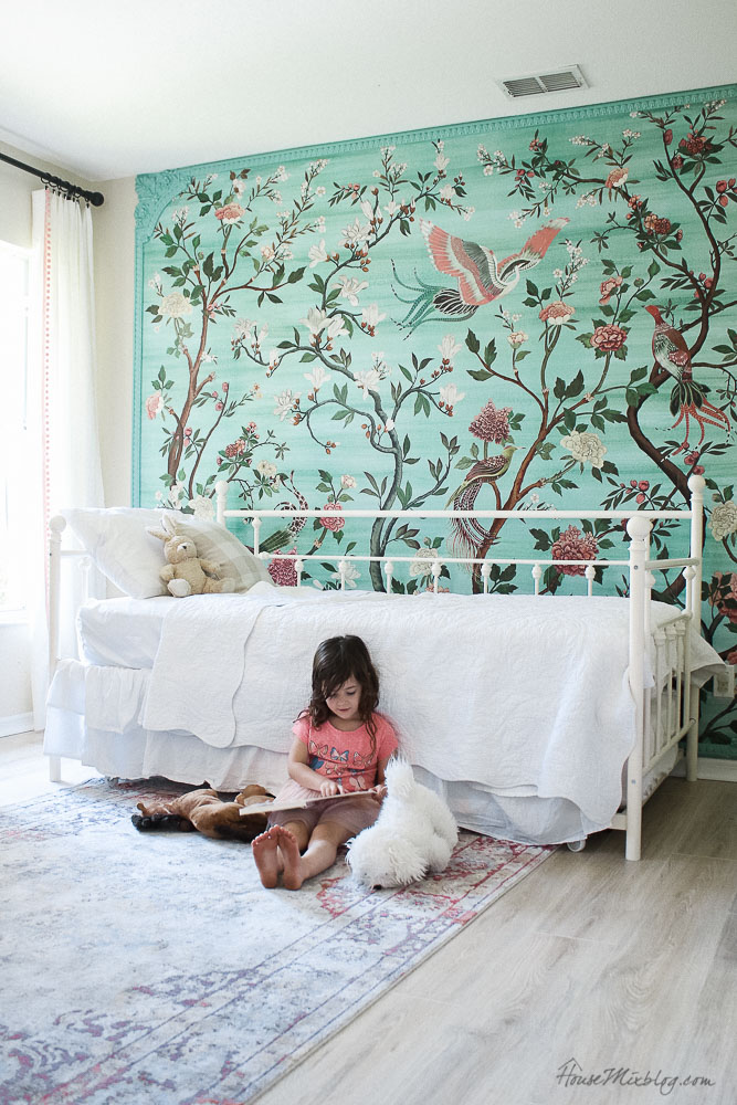 Green garden mural with flowers and birds in little girl's room- accent wall - girls room ideas - white vintage looking daybed with trundle - pink medallion rug