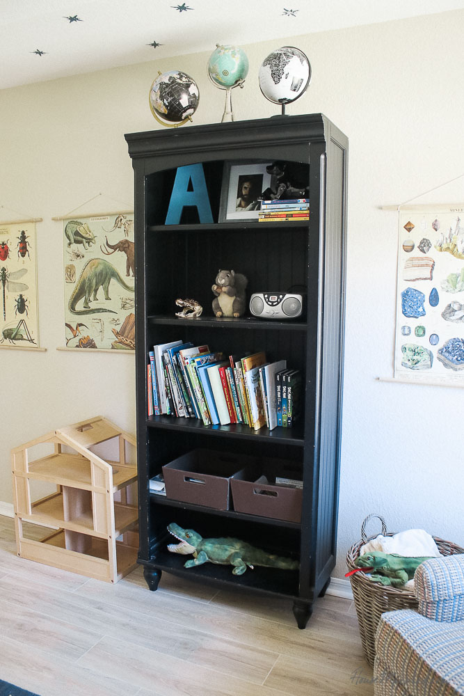 black bookcase in boys room - vintage posters - pale wood floor - globes - armchair - star ceiling - boys room styling