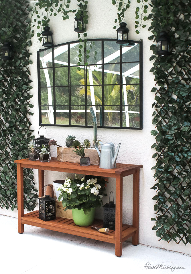 Patio, pool and lanai decor ideas on a budget- faux greenery, potting bench, mirror, lanterns with remote control candles