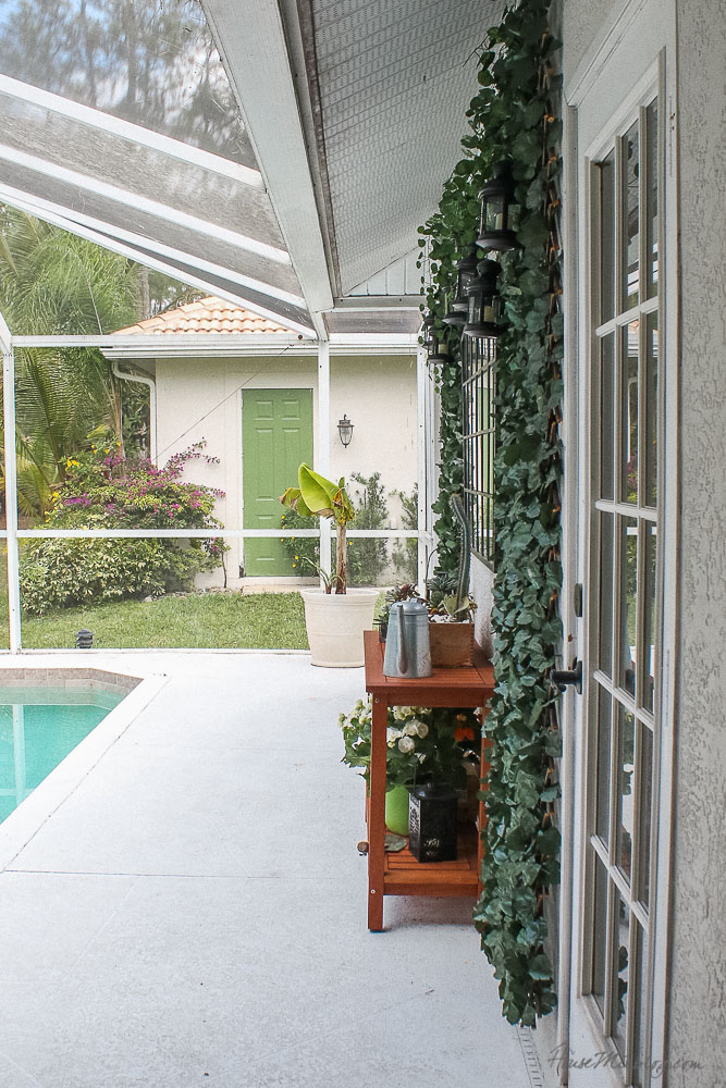 Patio, pool and lanai decor ideas on a budget-faux ivy screens, mirro and console table fill out a blank outdoor concrete wall