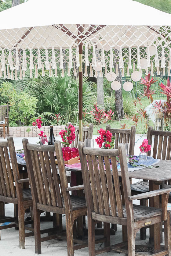 Table setting outside - Outdoor dining in hot pink and purple- bougainvillea and umbrella with fringe