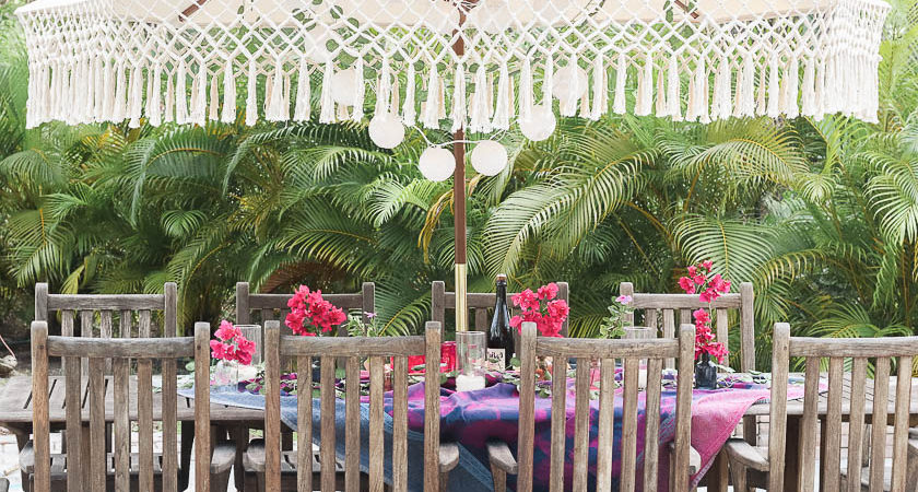 Table setting outside - Outdoor dining in hot pink and purple- outdoor umbrella with fringe and paper lantern string