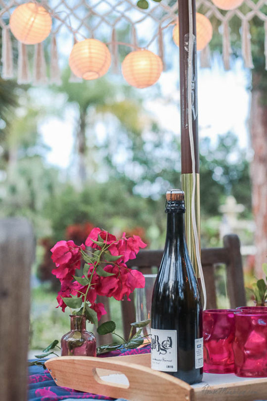 Table setting outside - Outdoor dining in hot pink and purple- romantic tablescape with fringe umbrella and candles with rice lanterns