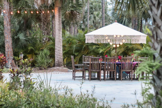Table setting outside - Outdoor dining in hot pink and purple-string lights and teak dining table with fringe umbrella