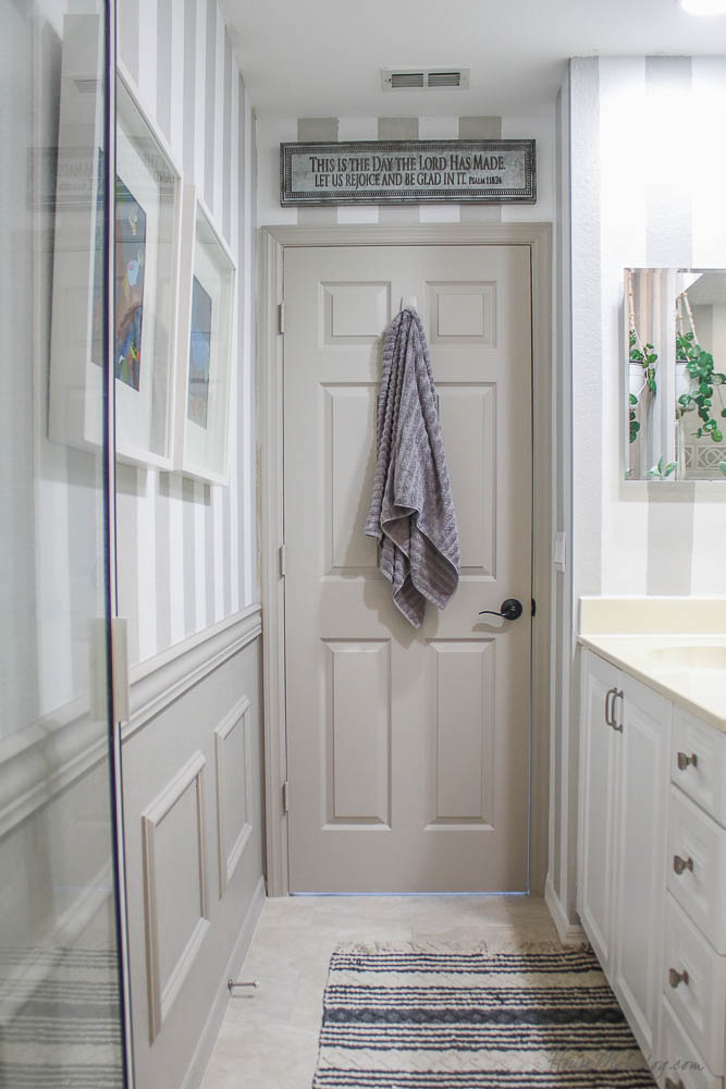 Gray and white striped boys bathroom with French gray wainscoting and door