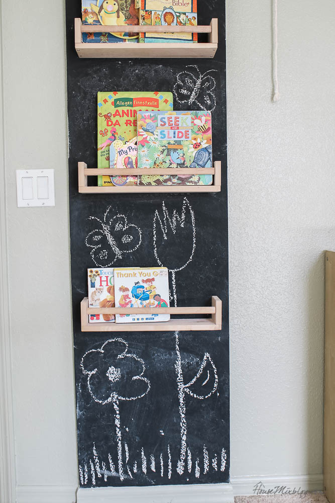 Chalkboard wall in playroom with $5 Ikea spice racks as bookshelves