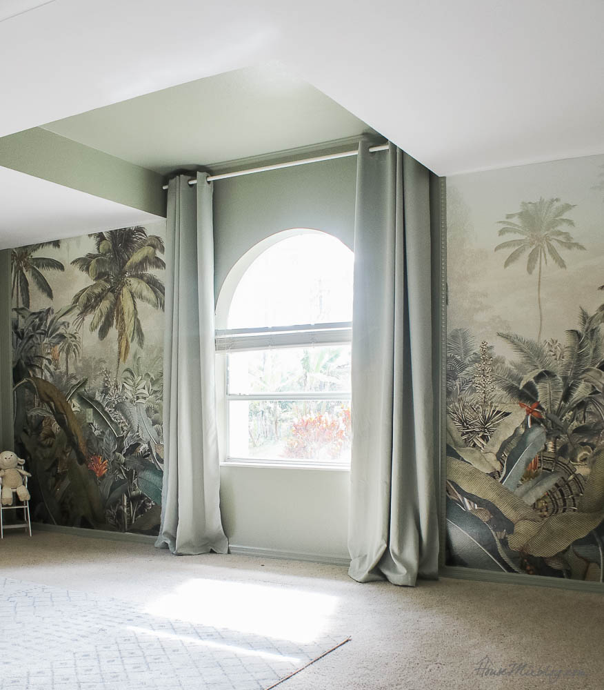 Sage playroom with tropical jungle mural and chalkboard wall with movie projector and wall. Benjamin Moore sage wisdom paint color. Matching $30 blackout curtains from Amazon