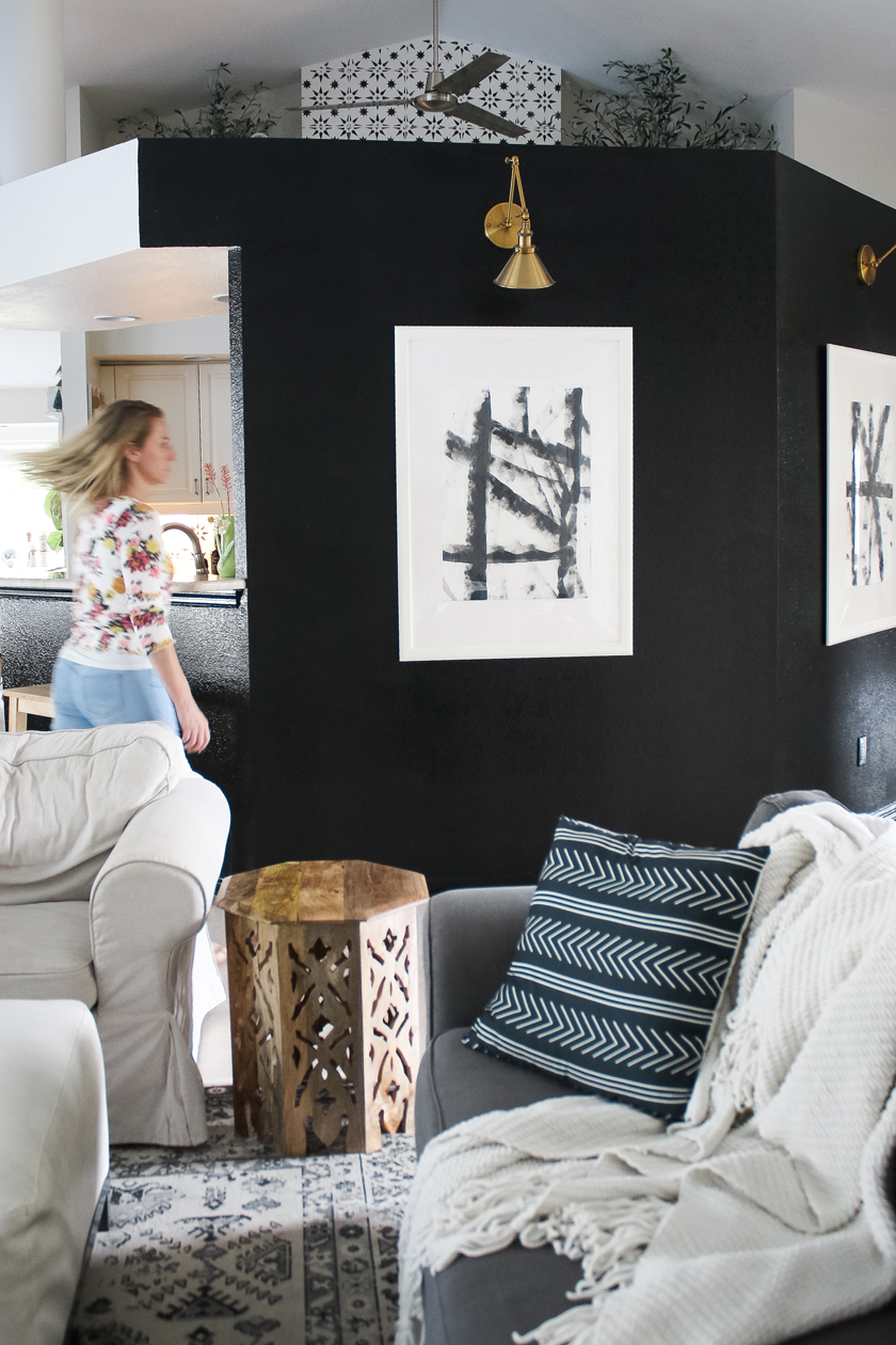 Black accent wall in living room with DIY art