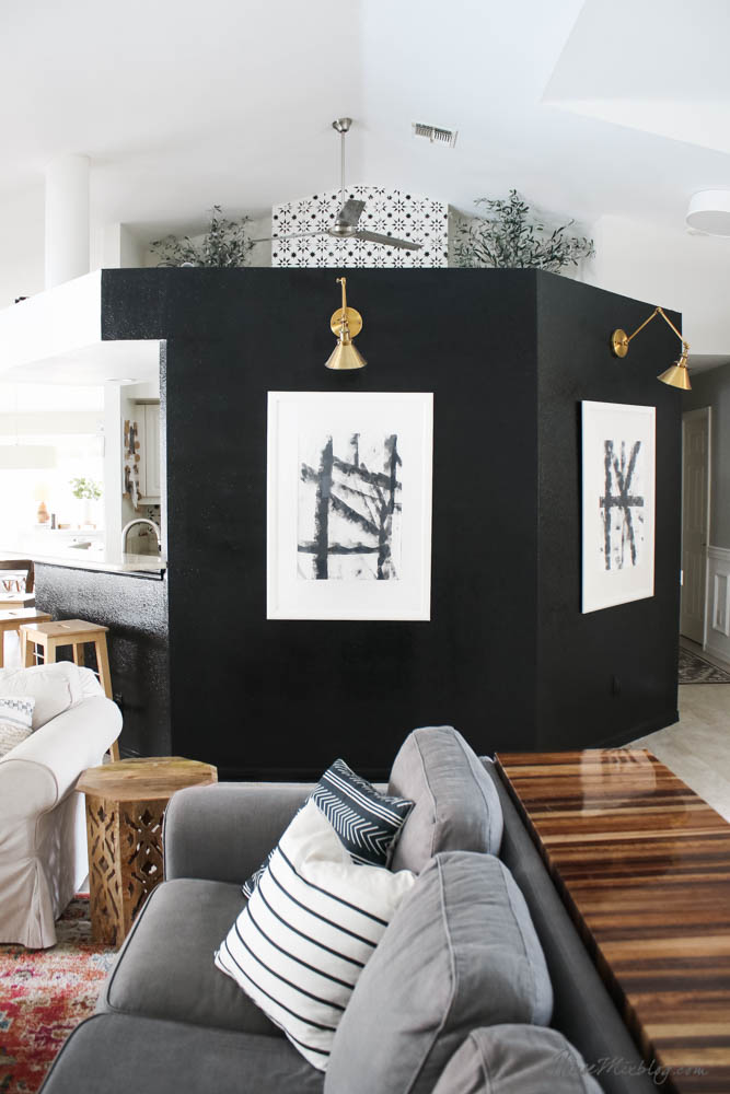 Black accent wall - living room with DIY black and white art and gold sconces