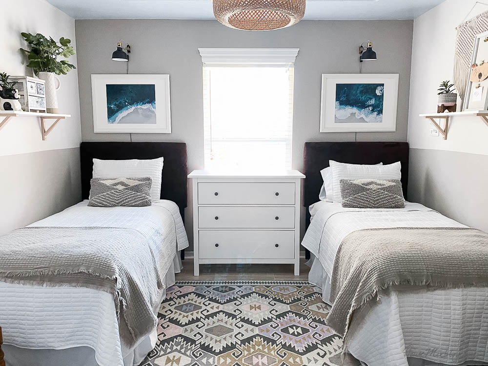 Bedroom with twin beds and ocean mural - sconces, water art, pale wood floor, aztec rug, french gray, blue and gray and white - neutral guest room
